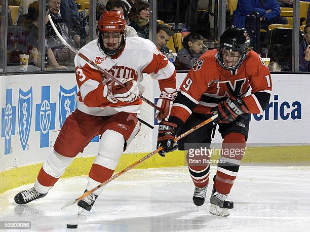 Kevin Schaeffer of the Boston University Terriers and Jared Mudryk of the Northeastern Huskies fight for possession of the puck during the 2005...