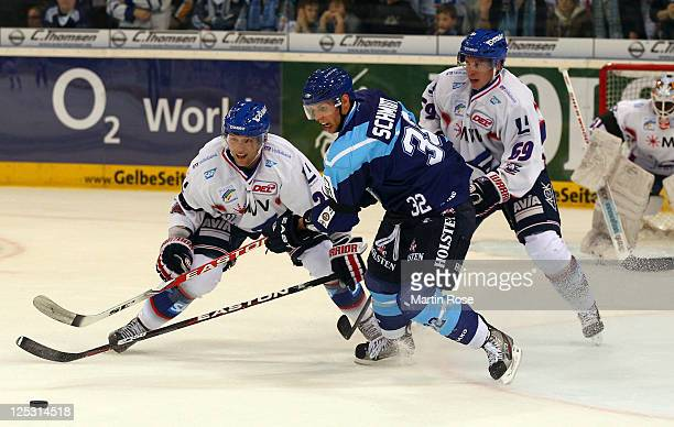 Kevin Schmidt of Hamburg vies for the puck with James Sifers of Mannheim during the DEL match between Hamburg Freezers and Adler Mannheim at the O2...