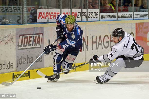 Kevin Schmidt of Iserlohn and John Mitchell of Nuernberg battle for the ball during the DEL match between Iserlohn Roosters and Thomas Sabo Ice...