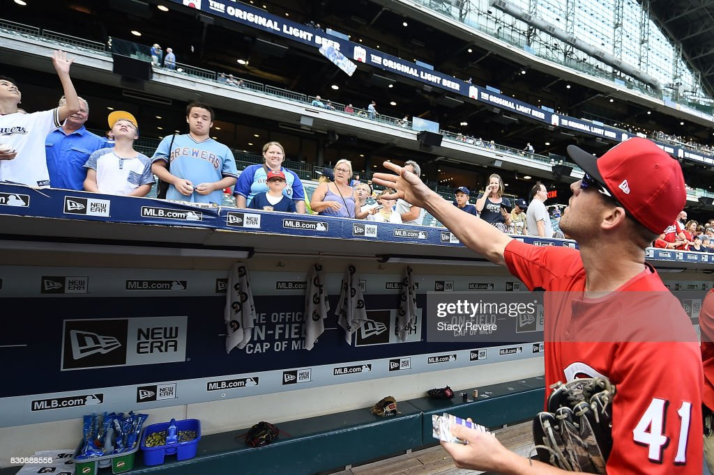 Kevin Shackelford #41 of the Cincinnati Reds hands out Topp's Baseball cards to fans prior to a game against the Milwaukee Brewers at Miller Park on August 12, 2017 in Milwaukee, Wisconsin.