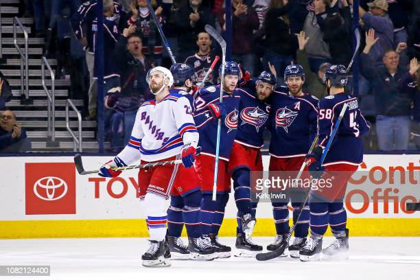 Kevin Shattenkirk of the New York Rangers skates off of the ice as Nick Foligno of the Columbus Blue Jackets is congratulated by his teammates after...