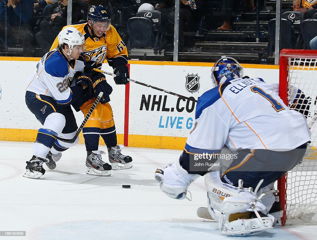 Kevin Shattenkirk #22 of the St. Louis Blues checks Victor Bartley #64 of the Nashville Predators off the puck during an NHL game at the Bridgestone Arena on April 9, 2013 in Nashville, Tennessee.