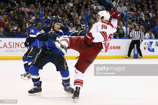 Kevin Shattenkirk of the St Louis Blues defends against Antoine Vermette of the Phoenix Coyotes at the Scottrade Center on April 6 2012 in St Louis...