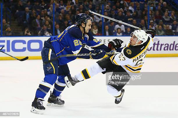 Kevin Shattenkirk of the St Louis Blues pushes Brad Marchand of the Boston Bruins to the ice at the Scottrade Center on February 6 2014 in St Louis...