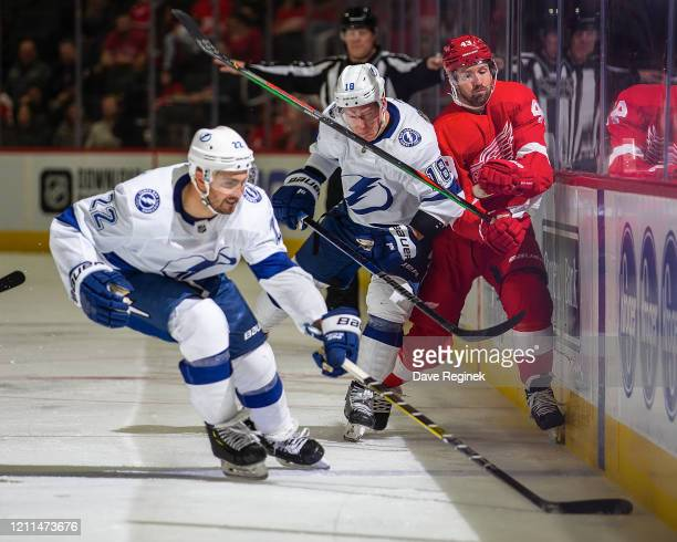 Kevin Shattenkirk of the Tampa Bay Lightning skates after a loose puck as teammate Ondrej Palat body checks Darren Helm of the Detroit Red Wings...