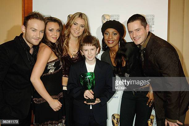 Kevin Simm Michelle Heaton Jessica Taylor Kelli Young and Tony Lundon of the band Liberty X with Freddie Highmore pose in the awards room with the...
