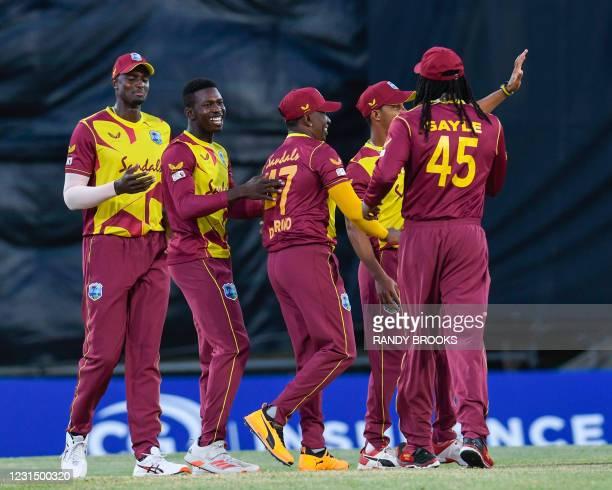 Kevin Sinclair and Jason Holder of West Indies celebrates the dismissal of Danushka Gunathilaka of Sri Lanka during a T20i match between Sri Lanka...