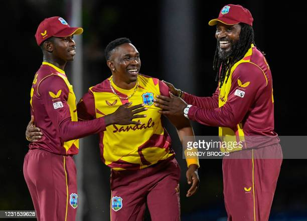 Kevin Sinclair , Dwayne Bravo and Chris Gayle of West Indies celebrate the dismissal of Pathum Nissanka of Sri Lanka during the 2nd T20i match...