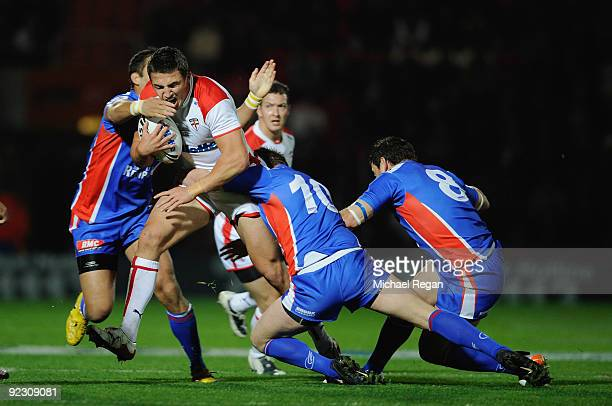 Kevin Sinfield of England is tackled by Olivier Elima Remi Casty and David Ferriol of France during the Gillette Four Nations match between England...