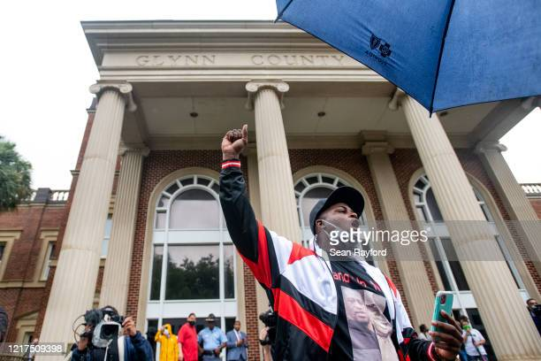 Kevin Smith demonstrates outside the Glynn County courthouse during a court appearance by Gregory and Travis McMichael, two suspects in the fatal...