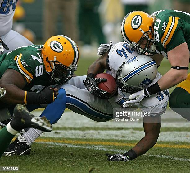 Kevin Smith of the Detroit Lions is tackled by Ryan Pickett and A.J. Hawk of the Green Bay Packers at Lambeau Field on October 18, 2009 in Green Bay,...