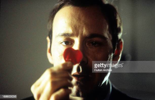 Kevin Spacey staring at a rose pedal in a scene from the film 'American Beauty' 1999