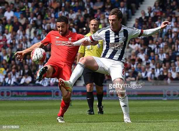 Kevin Stewart of Liverpool competes with Craig Gardner of West Bromwich Albion during the Barclays Premier match between West Bromwich Albion and...