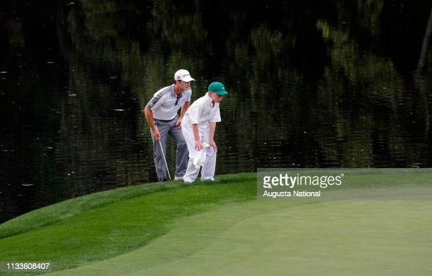 Kevin Streelman and his caddie Ethan Couch line up a putt on the No 9 to win in a playoff during the Par 3 Contest for the Masters at Augusta...