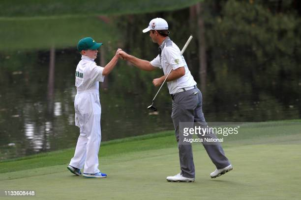 Kevin Streelman celebrates with his caddie Ethan Couch after Streelman made a putt to win the he Par 3 Contest for the Masters at Augusta National on...