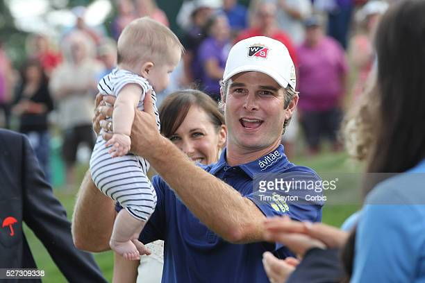 Kevin Streelman holding his 6monthold daughter Sophia watched by his wife Courtney after winning the Travelers Championship at the TPC River...