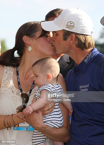 Kevin Streelman kisses his wife Courtney who is holding their 6monthold daughter Sophia after winning the Travelers Championship at the TPC River...