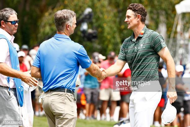 Kevin Streelman of the United States and Justin Rose of England shake hands on the 18th green during the final round of the Wyndham Championship at...