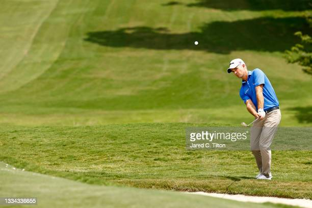 Kevin Streelman of the United States chips to the 18th green during the final round of the Wyndham Championship at Sedgefield Country Club on August...