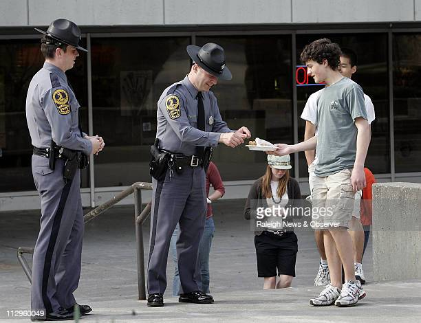 Kevin Sullivan, a high-school student from Blacksburg gives away chocolate chip cookies to Virginia State Police officers Russell Edwards and Josh...
