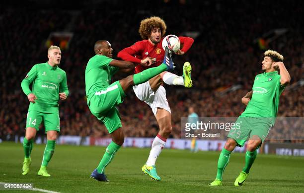 Kevin Theophile Catherine of SaintEtienne tackles Marouane Fellaini of Manchester United during the UEFA Europa League Round of 32 first leg match...