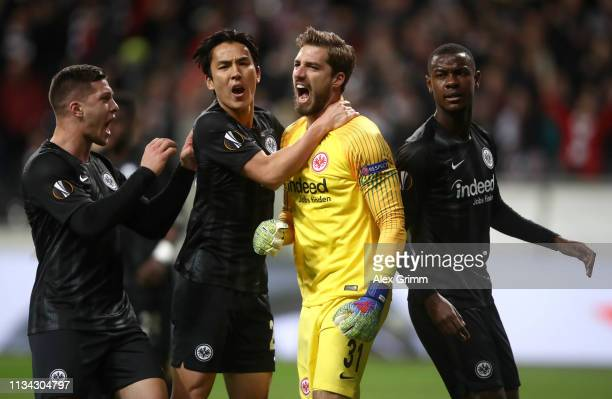Kevin Trapp of Eintracht Frankfurt is congratulated by his team mates Luka Jovic of Eintracht Frankfurt Makoto Hasebe of Eintracht Frankfurt and Evan...