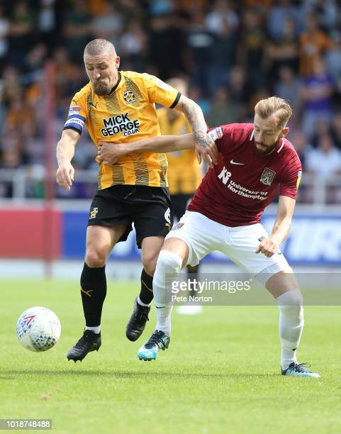 Kevin van Veen of Northampton Town looks to move forward with the ball away from Brad Halliday of Cambridge United during the Sky Bet League Two...