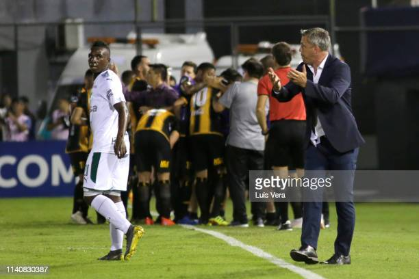 Kevin Velasco receives instructions from his coach Lucas Pusineri of Deportivo Cali while in the back players of Guarani celebrate their first goal...