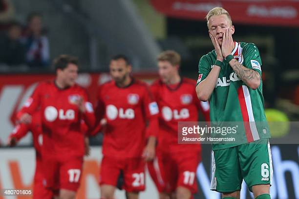 Kevin Vogt of Augsburg reacts whilst players of Leverkusen celebrate their 3rd team goal during the Bundesliga match between FC Augsburg and Bayer...
