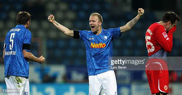 Kevin Vogt of Bochum celebrates with Christoph Dabrowski next to Markus Brzenska of Cottbus after winning the Second Bundesliga match between VfL...