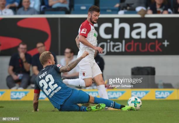Kevin Vogt of Hoffenheim tackles Marcel Heller of Augsburg during the Bundesliga match between TSG 1899 Hoffenheim and FC Augsburg at Wirsol...