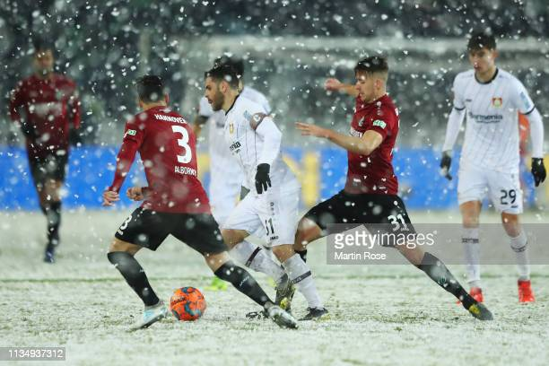 Kevin Volland of Bayer 04 Leverkusen battles for the ball with Miiko Albornoz and Waldemar Anton of Hannover 96 during the Bundesliga match between...