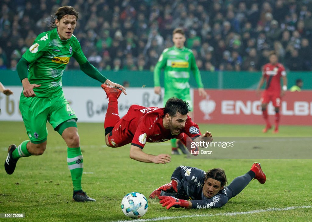 Kevin Volland of Bayer Leverkusen is challenged by Jannik Vestergaard of Moenchengladbach and Yann Sommer of Moenchengladbach during the DFB Cup match between Borussia Moenchengladbach and Bayer Leverkusen at Borussia-Park on December 20, 2017 in Moenchengladbach, Germany.