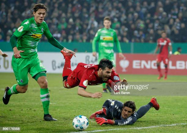 Kevin Volland of Bayer Leverkusen is challenged by Jannik Vestergaard of Moenchengladbach and Yann Sommer of Moenchengladbach during the DFB Cup...