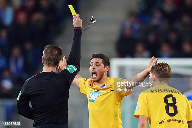 Kevin Volland of Hoffenheim reacts as referee Peter Gagelmann shows him the yellow card during the DFB Cup quarterfinal match between 1899 Hoffenheim...
