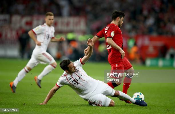 Kevin Volland of Leverkusen and Mats Hummels of Muenchen battle for the ball during the DFB Cup semi final match between Bayer 04 Leverkusen and...