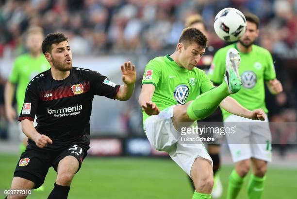 Kevin Volland of Leverkusen challenges Robin Knoche of Wolfsburg during the Bundesliga match between Bayer 04 Leverkusen and VfL Wolfsburg at...