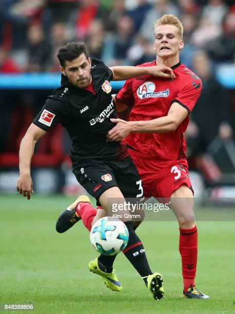 Kevin Volland of Leverkusen is challenged by Philipp Lienhart of Freiburg during the Bundesliga match between Bayer 04 Leverkusen and SC Freiburg at...