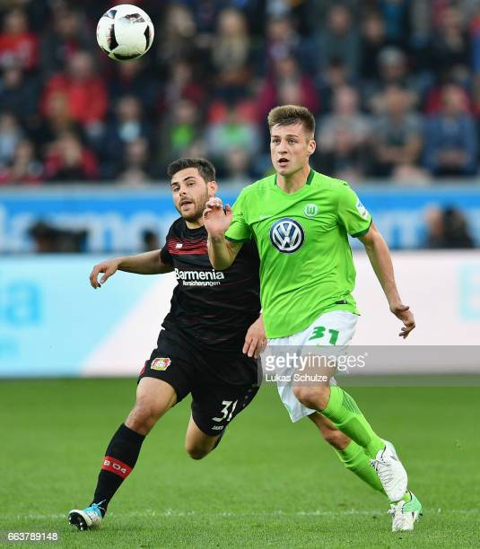 Kevin Volland of Leverkusen is challenged by Robin Knoche of Wolfsburg during the Bundesliga match between Bayer 04 Leverkusen and VfL Wolfsburg at...