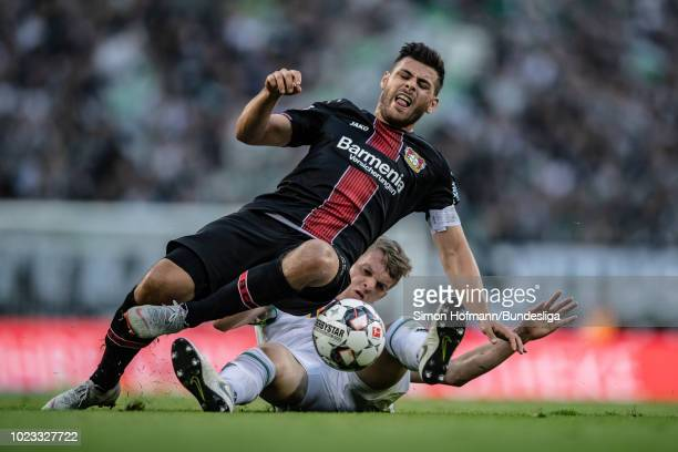 Kevin Volland of Leverkusen is tackled by Matthias Ginter of Moenchengladbach during the Bundesliga match between Borussia Moenchengladbach and Bayer...