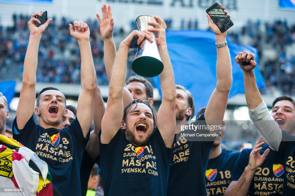 Kevin Walker of Djurgardens IF raises the Swedish Cup as his teammates celebrate winning the Svenska Cupen Final between Djurgardens IF and Malmo FF at Tele2 Arena on May 10, 2018 in Stockholm, Sweden.