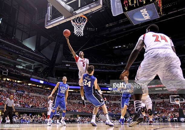 Kevin Ware of the Louisville Cardinals drives for a shot attempt against Ryan Kelly of the Duke Blue Devils during the Midwest Regional Final round...