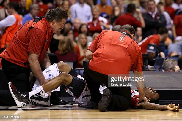 Kevin Ware of the Louisville Cardinals is tended to by medical personnel after he injured his leg in the first half against the Duke Blue Devils...