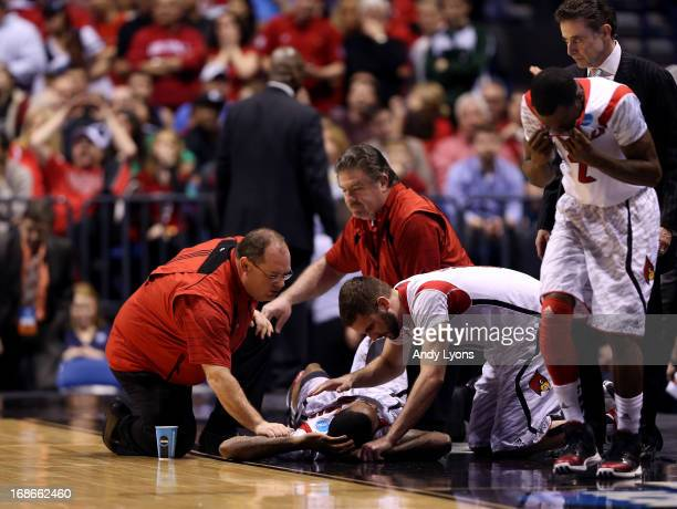 Kevin Ware of the Louisville Cardinals talks with teammate Luke Hancock as Ware is tended to by medical personnel after he injured his leg in the...