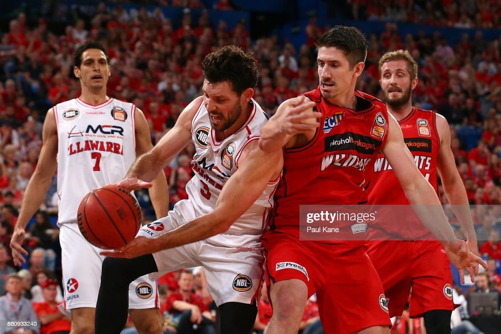 Kevin White of the Hawks gathers the ball against Greg Hire of the Wildcats during the round two NBL match between the Perth Wildcats and the Illawarra Hawks at Perth Arena on October 13, 2017 in Perth, Australia.