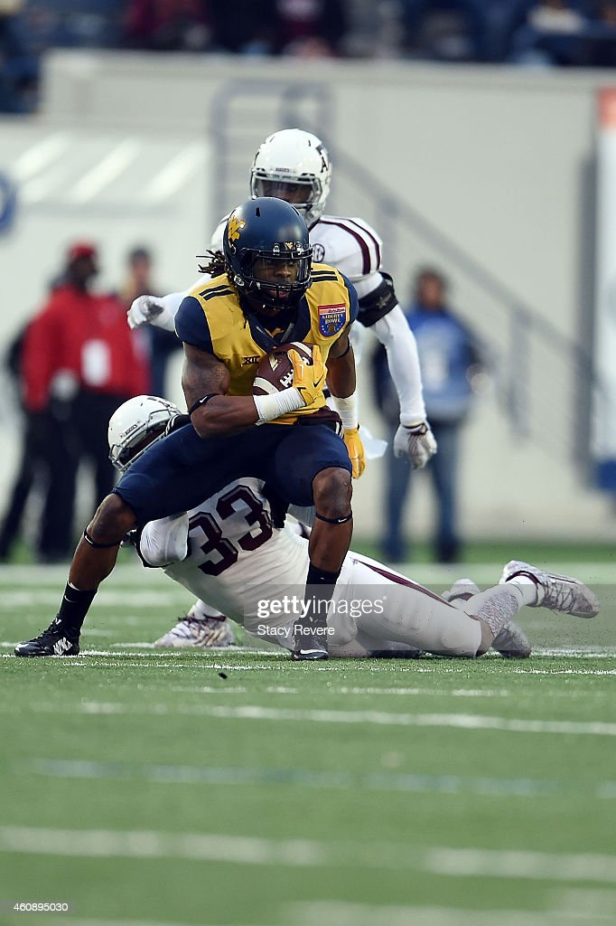 Kevin White #11 of the West Virginia Mountaineers is brought down by Shaan Washington #33 of the Texas A&M Aggies during the third quarter of the 56th annual Autozone Liberty Bowl at Liberty Bowl Memorial Stadium on December 29, 2014 in Memphis, Tennessee.