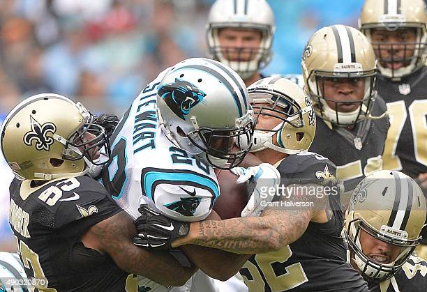 Kevin Williams and Kenny Vaccaro of the New Orleans Saints tackle Jonathan Stewart of the Carolina Panthers during their game at Bank of America...