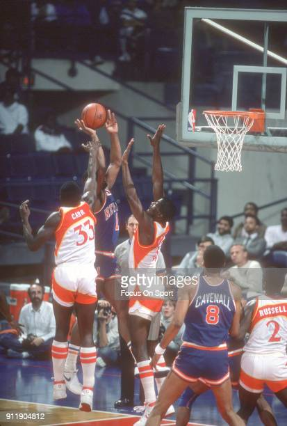 Kevin Willis and Antoine Carr of the Atlanta Hawks goes up to defend the shot of Ken Banister of the New York Knicks during an NBA basketball game...