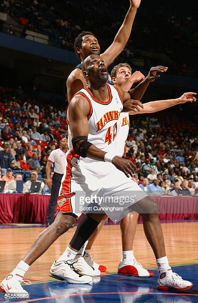 Kevin Willis and Chris Crawford of the Atlanta Hawks attempt to rebound over Michael Olowokandi of the Minnesota Timberwolves during the preseason...