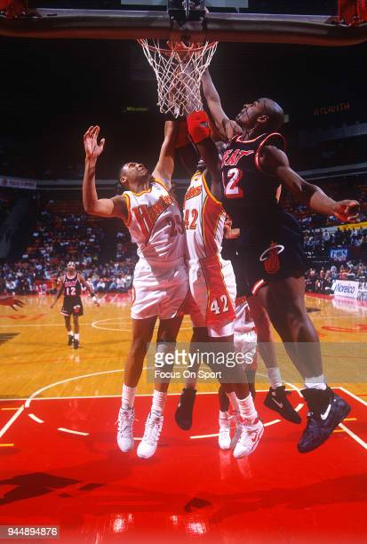 Kevin Willis and Doc Rivers of the Atlanta Hawks battles for a rebound with Bimbo Coles of the Miami Heat during an NBA Basketball game circa 1992 at...